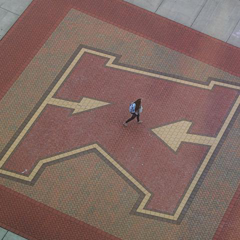 A 肯特 State University student walks on the K in Risman Plaza.