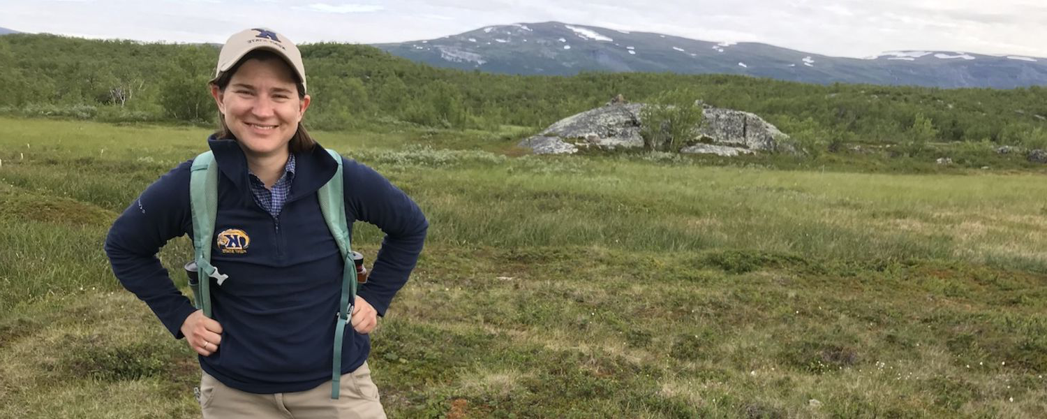 Lauren Kinsman-Costello, assistant professor of biological sciences at Kent State, stands in a field in the arctic circle, in Sweden.